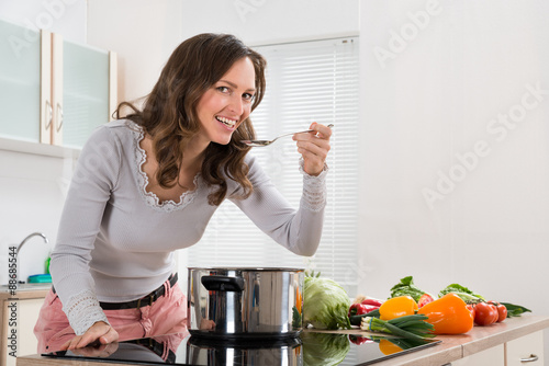 Poster Cuisine Woman Smiling While Tasting Meal In Kitchen