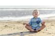 jongen mediteert op het strand aan zee