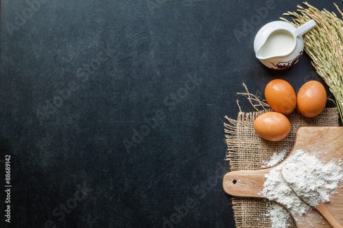 Fotografie, Obraz  Baking powder milk and eggs on chalkboard for background