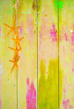 Yellow Colorful Vintage Background With Shabby Distressed Grungy Texture Hippie Style Decorated With Yellow Starfish Hanging From A Straw String.