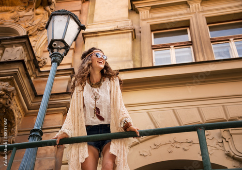 Fotografering  smiling boho chic with sunglasses near old town streetlight