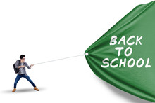 Male Student Pulling Banner Of Back To School