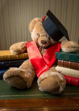 Brown Teddy Bear Wearing Graduation Cap Leaning On Books