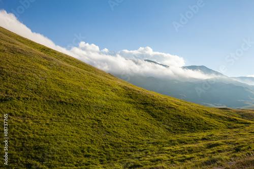 Tuinposter Heuvel Pendio di montagna, nella luce del tramonto. Cielo blu con nuvole sullo sfondo
