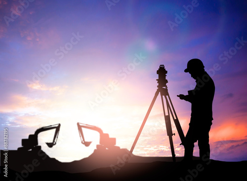 Fotografie, Obraz  silhouette survey engineer working  in a building site over Blur