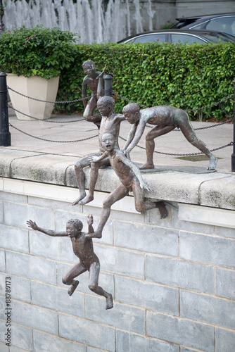 Photo  Raffles place, a statue of kids jumping to the river