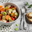 meat stew with vegetables - carrots, onions and sweet peppers in a white bowl on a light wooden background