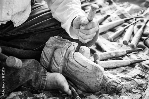 Photo Hand of carver carving wood in black and white color tone