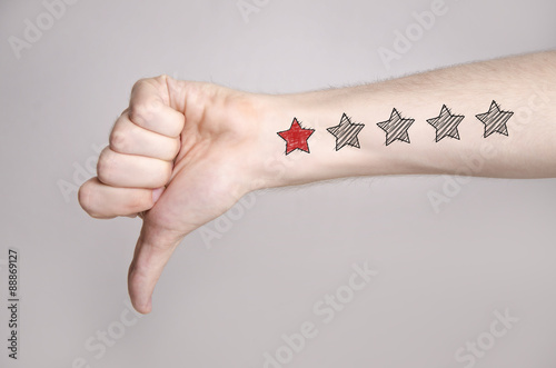 Fotografie, Obraz  Man hand showing thumbs down and one star rating on the arm skin