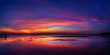 canvas print picture - Sunset on fire. Really bright and colorful sunset at the sea with reflection of the skies in the water.