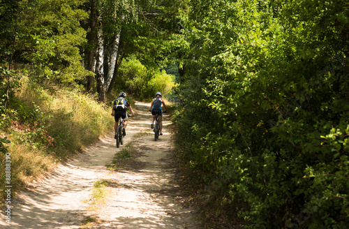 Fotobehang Fietsen couple cycling with helmets in the hot summer on the green forest trai