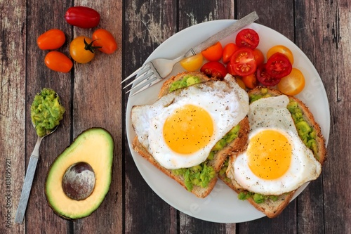 Fototapeta Healthy avocado, egg open sandwiches on a plate with cherry tomatoes on rustic wood obraz
