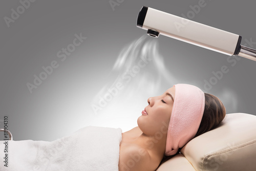 Fotografie, Obraz  Beauty treatment of face skin with ozone facial steamer in spa center , asian women facing the steam