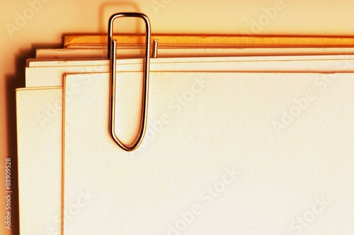 view of a paper clip with stack of blank paper Canvas Print