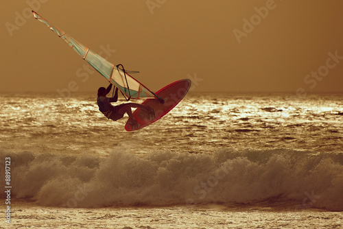 obraz lub plakat windsurfer jumping in a sunset sky