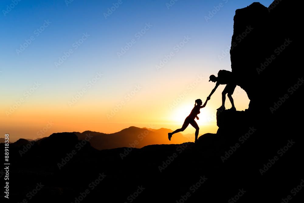 Fototapeta Teamwork couple climbing helping hand