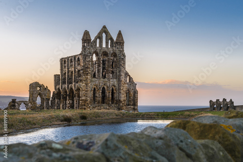 Poster Rudnes Stone ruins of Whitby Abbey on the cliffs of Whitby, North Yorkshire, England at sunset.