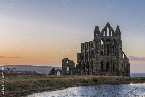 Poster Ruine Stone ruins of Whitby Abbey on the cliffs of Whitby, North Yorkshire, England at sunset.