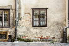 Wall On European City Street With Windows And Crumbling Plaster.