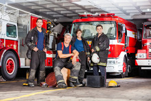 Happy Firefighter's Team With Equipment At Fire Station
