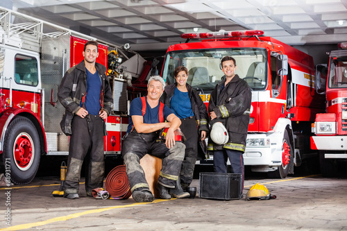 Happy Firefighter's Team With Equipment At Fire Station Canvas Print