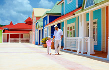 Happy Father And Son Walking On Caribbean Village Street