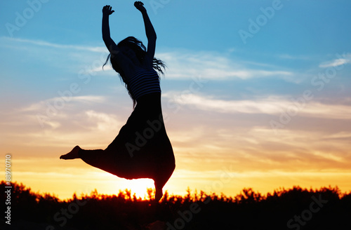 Fotografie, Obraz  Silhouette of a beautiful girl jumping over sunset