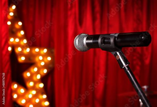Fotografie, Obraz  Mikrofon na divadelním jevišti, zlatá hvězda na pozadí s červenými závěsy