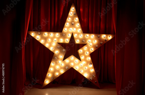Photo of golden star with light bulbs on red velvet curtain on stage Canvas Print