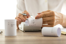 Woman Doing Calculations On An Adding Machine Or Calculator Pulling Off Reams Of Paper With Printed Figures And Totals, Conceptual Of Accounting A Bookkeeping, Close Up Of Her Hands.