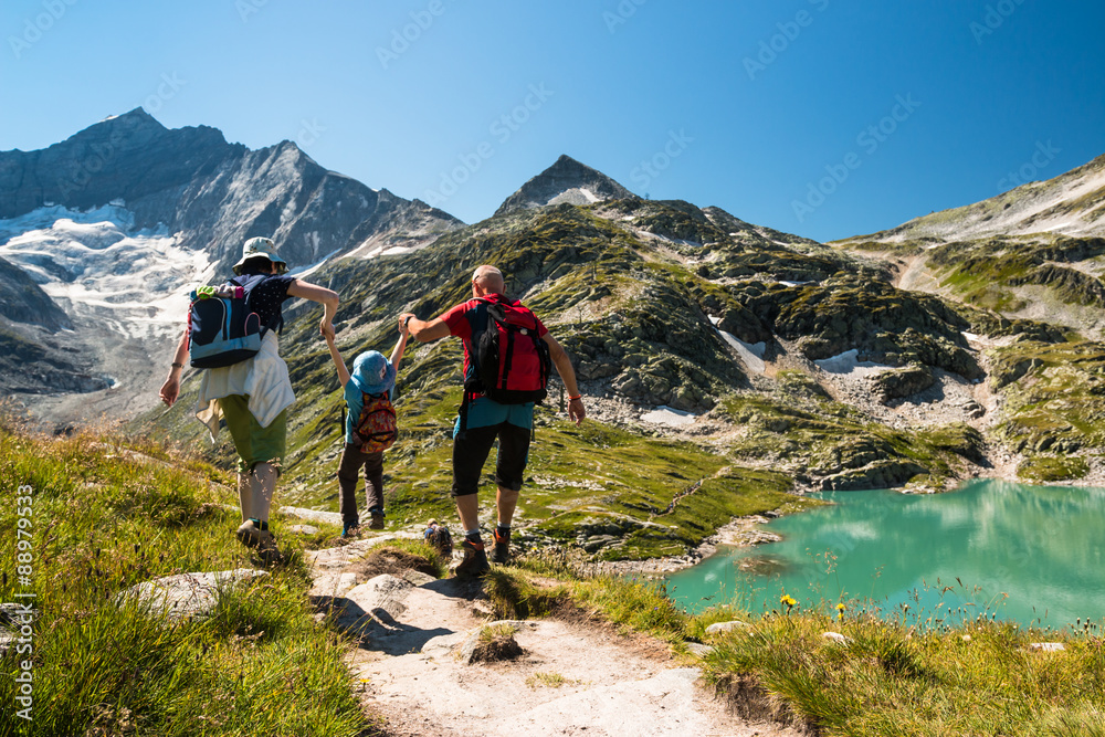 Fototapeta family with child hiking on holiday in austrian alps with lake and glacier view