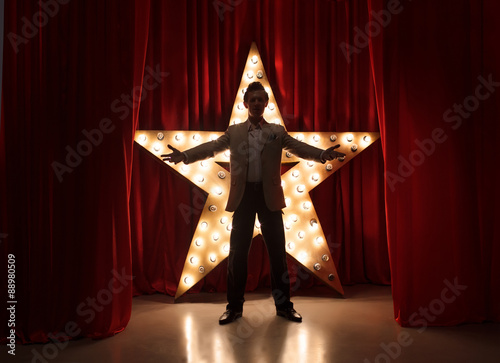 Man on stage with star on background Canvas Print