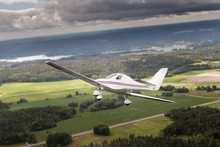A Small Motor Airplane Flying Above Landscape