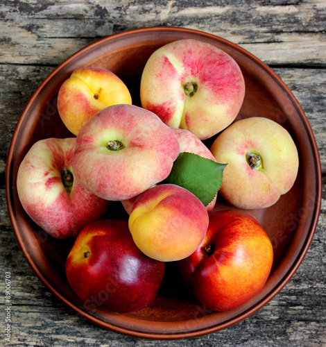 Beautiful peaches, apricots and nectarines on a plate on a wooden background