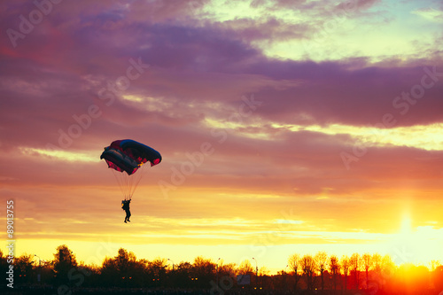 Poster de jardin Aerien Skydiver On Colorful Parachute In Sunny Sky