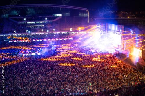 Plakat Szczęśliwi ludzie klaskali na nocnym koncercie, imprezując i podnosząc ręce dla artysty na scenie. Rozmyty widok z lotu ptaka koncertu tłum