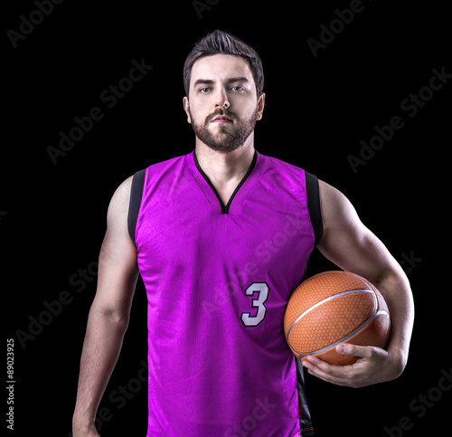 Foto  Basketball Player on a purple uniform on black background