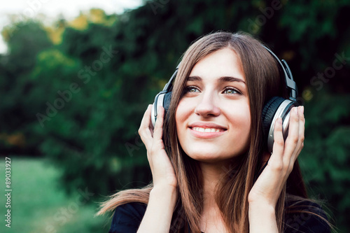 Beautiful young girl listening to music on headphones. The girl in the park .