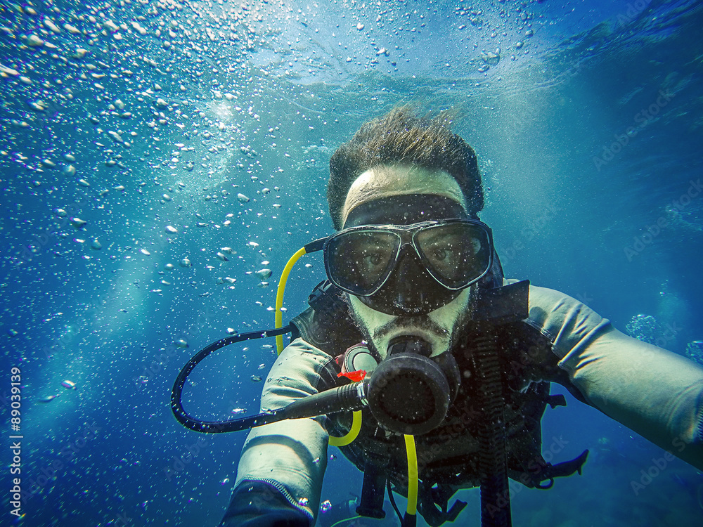 Fototapeta Diving. Self portrait of young diver in the sea. Blue water background.