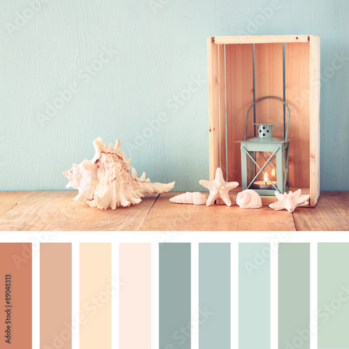 Carta da parati sea shells and lantern on wooden table with palette color swatches
