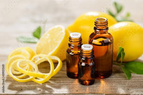 Fotografie, Obraz  lemon essential oil and lemon fruit on the wooden board, (taken with tilt shift