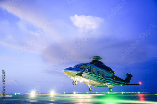 Photo Stands Helicopter helicopter parking landing on offshore platform. Helicopter transfer crews or passenger to work in offshore oil and gas industry.Night flight training of Pilot and coordinate pilot.