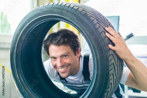 Fotografia, Obraz  Mechaniker tauscht Auto Reifen bei Reifenwechsel in Kfz-Werkstatt