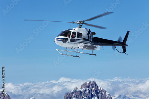 Poster Helicopter Scenic helicopter flies over the tops of the Marmolada, in front of the rope to the top of the cab. Italy