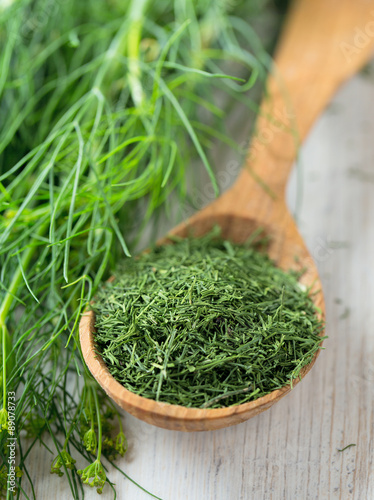 Obraz na plátne dried dill in a wooden spoon