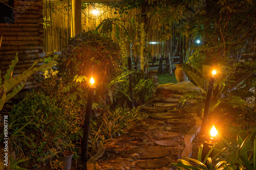Foto op Canvas Tuin lamp with walkway in the garden night time