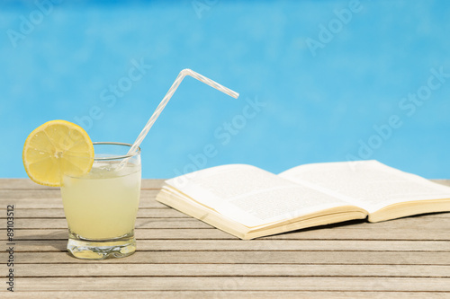 Carta da parati Glass of iced lemonade and opened book on the table - poolside