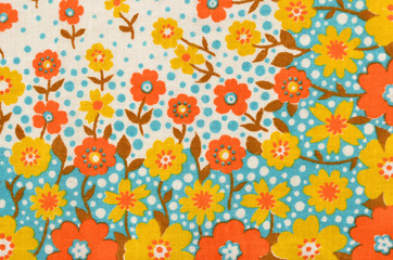 Floral pattern on fabric. Yellow and orange flowers with blue dots print as background.