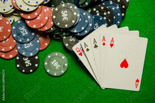 Playing cards 'Four of a kind' and chips on green background плакат