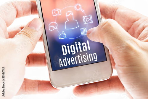 Fotografía  Cerca mano móvil que sostiene con la publicidad y los iconos digital,